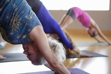 Females practicing yoga in exercise studio