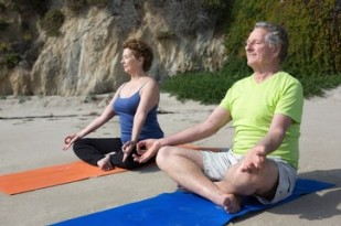 Caucasian couple meditating on beach